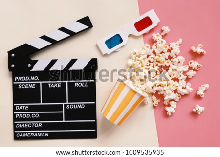 Flat lay of cinema movie items, clapperboard, 3d glasses and popcorn on colorful bright background, entertainment concept