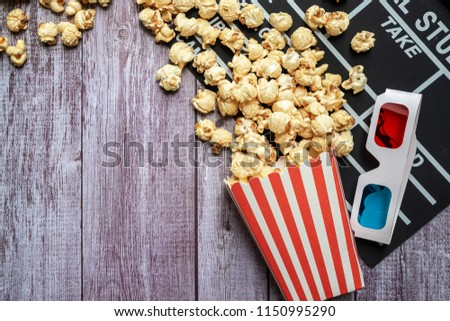 Flat lay of cinema movie items, clapperboard, 3d glasses and popcorn on wooden background, entertainment concept