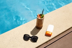 Flat lay of cocktail in wooden container, black fashionable sunglasses and sun protection cream in white bottle, making up composition for rest during vacation. Things are situated near swimming pool.