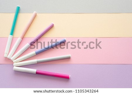 Flat-lay of colorful pastel markers on pastel color background with empty space for text.