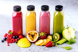 Flat-lay of colorful smoothies in bottles with fresh tropical fruit and superfoods on concrete background