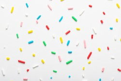 flat lay of colorful sprinkles over white background, festive decoration for banner, poster, flyer, card, postcard, cover, brochure