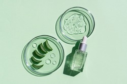 Flat lay of cosmetics serum and and laboratory glassware with fresh leaves of aloe vera on bright green background. Organic cosmetics. Top view flat lay, copy space. Cosmetics, SPA branding, mock-up.