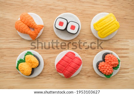 Flat lay of cute Japanese food eraser toy set on wooden background minimal style. Kid learning, development and funny play by small eraser toy in school accessories. ストックフォト ©