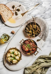 Flat-lay of different Mediterranean vegetarian meze in copper dishes, olive oil and fresh bread over marble table background, top view. Aegean cuisine concept