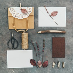 Flat lay of different object on vintage background. Craft brown bag, empty blank and tools. DIY concept. Homemade invitation card. Rustic style for wedding
