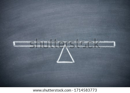 Flat lay of drawing empty seesaw or balance scale in equilibrium on chalkboard or blackboard background with copy space. Concept of decision, comparison and measuring. Сток-фото ©