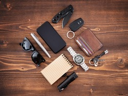 Flat lay of EDC or Every Day Carry items and tools on wooden background