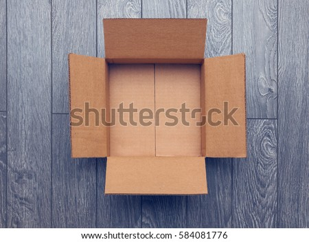 Flat lay of empty open cardboard box on wooden surface #584081776