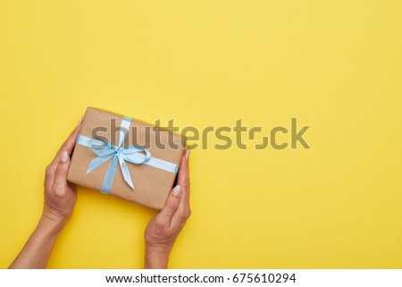 Flat lay of fantastic wrapped present decorated with bow on yellow background