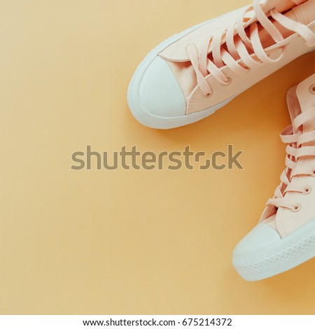 Flat lay of female sneakers on a pale peach pastel background with copy space #675214372