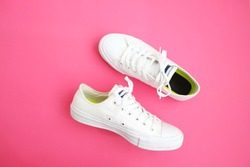 Flat lay of female sneakers on a pink background. Place for your design, text