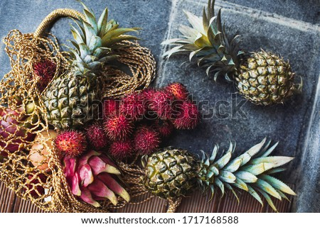 Flat lay of fresh tropical fruits pineapple, rambutan, dragon fruit in reusable mesh bag. Zero waste lifestyle. Raw healthy food and vegetarian diet. Taste of summer.