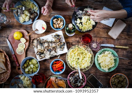Flat-lay of friends hands eating and drinking together.Food Catering.Buffet Party Concept.having party, gathering,celebrating together at wooden rustic table set with different wine snacks. top view #1093952357