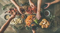 Flat-lay of friends hands eating and drinking together. Top view of people having party, gathering, celebrating together at wooden rustic table set with different wine snacks and fingerfoods