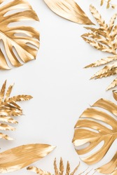 Flat lay of golden tropical leaf design elements. Decoration elements for invitation, wedding cards, valentines day, greeting cards. isolated over white background. Top view