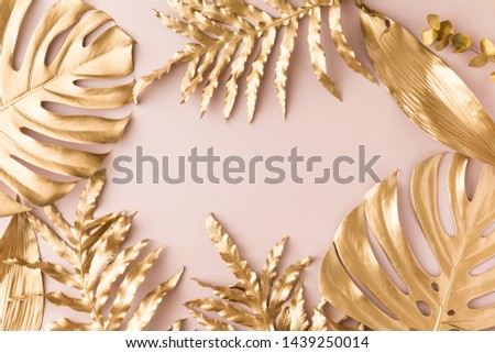 Flat lay of golden tropical leaf design elements. Decoration elements for invitation, wedding cards, valentines day, greeting cards. isolated on pink background. Top view #1439250014