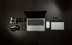 Flat Lay of Hipster freelance designer and analog photographic equipment on a wooden dark desktop with laptop, hard drive, tablet for graphic design and mouse.