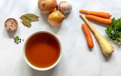 Flat lay of homemade beef bone broth in a bowl with ingredients. Contains minerals and healthy nutrients, including vitamins, amino acids, and essential fatty acids.