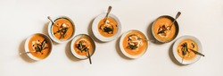 Flat-lay of homemade fall pumpkin cream soup in plates with sour cream, pumpkin seeds and bread croutons over plain white table background, top view. Healthy comfort food and clean eating
