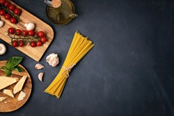 Flat lay of Ingredients for cooking italian pasta. Spaghetti, tomatoes, oil, garlic, parmezan. Top view of traditional italian cusine concept