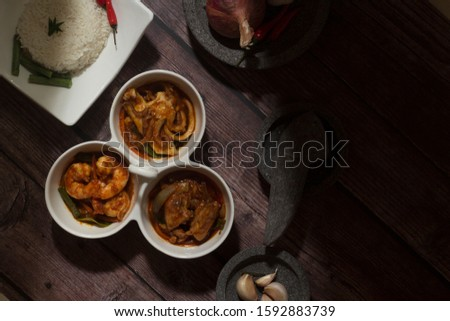 Flat lay of Malay traditional cuisine. Asian cuisine. Seafood spicy dishes. Shrimp and Squid curry.
