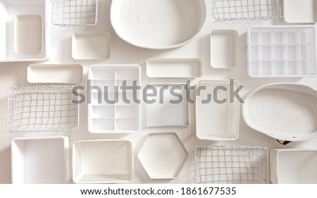 Flat lay of Marie Kondo's white storage boxes, containers and baskets with different sizes and shapes for tidying up wardrobe. KonMari method organizer boxes set. Closet organizing concept. Stockfoto ©