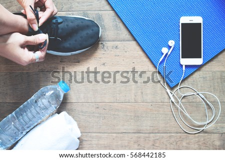 Flat lay of mobile phone with earphone and sport equipment on wood background. Woman in black sneaker with sport equipment, top view