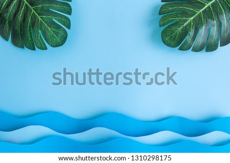 Flat lay of monstera palm leaves and sea waves against pastel blue sky background minimal creative concept.