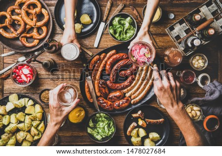 Flat-lay of Octoberfest party dinner table with grilled meat sausages, German pretzel pastry, potatoes, cucumber salad, sauces, beers and peoples hands with food over dark wooden background, top view Foto stock ©
