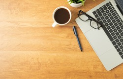 Flat lay of Office desk with laptop, and blank notepad with a coffee cup on wood table, copy space, top view