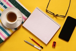 Flat lay of office desk with tablet, notebook, spectacles, coffee, pen, pencil and sharpner on yellow background. Take a break concept. Author, writer, ideas, business, plan, notes.