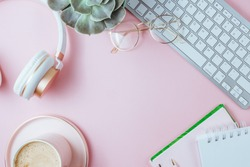 Flat lay of office feminine desk workspace with cup of coffee, succulent, laptop, empty notebook, headphones, keyboard, and golden eyeglasses on pink background. Top view. Copy space