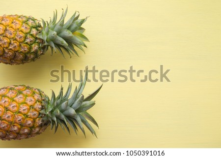 Flat lay of organic pineapples on yellow wooden background with copy space, tropical summer holiday vacation concept #1050391016