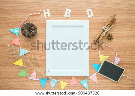 Flat lay of photo frame with happy birthday wooden alphabet mockup on wooden table