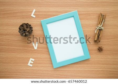 Flat lay of photo frame with love wooden alphabet mockup on wooden table