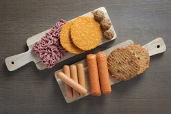 Flat lay of plant based vegetarian meat products for a plant based diet on a wooden table