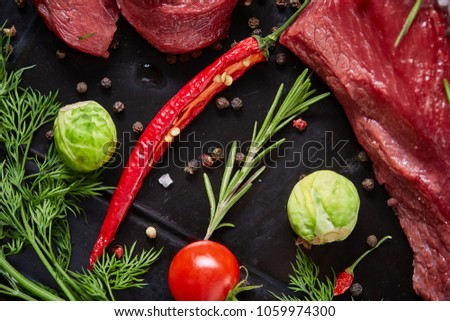 Flat lay of raw beefsteak with vegetables, herbs and spicies on metal tray, close-up, selective focus #1059974300