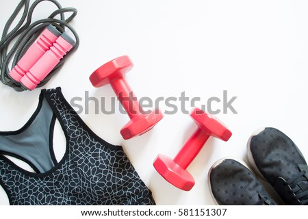 Flat lay of red dumbbell, sport bra, jump rope and sneaker, sport equipments, fitness items, top view