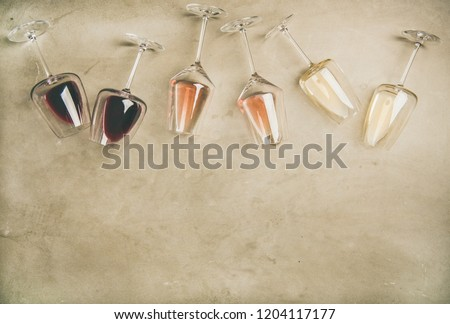 Flat-lay of red, rose and white wine in glasses and corkscrews over grey concrete background, top view, copy space. Wine bar, winery, wine degustation concept