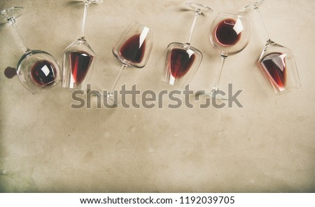Flat-lay of red wine in glasses over grey concrete background, top view, copy space. Bojole nouveau, wine bar, winery, wine degustation concept