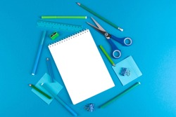 Flat lay of school office supplies on blue background with blank space for text