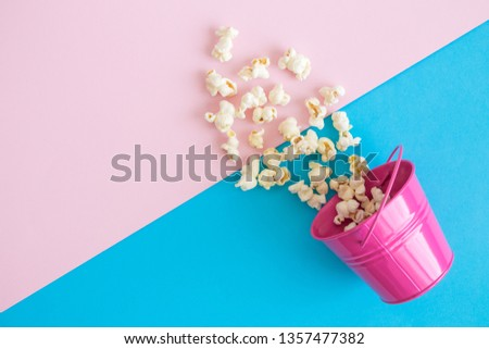 Flat lay of small metal bucket with spilled popcorn on pastel background minimal creative concept. #1357477382