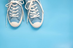 Flat lay of soft blue color canvas shoe on blue background with copy space