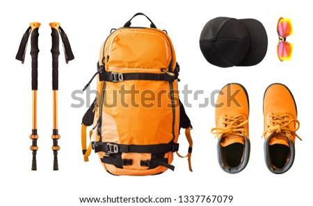 Flat lay of sport equipment and clothes for hiking and trekking. Top view of walking poles, backpack, boots, etc. isolated on white background