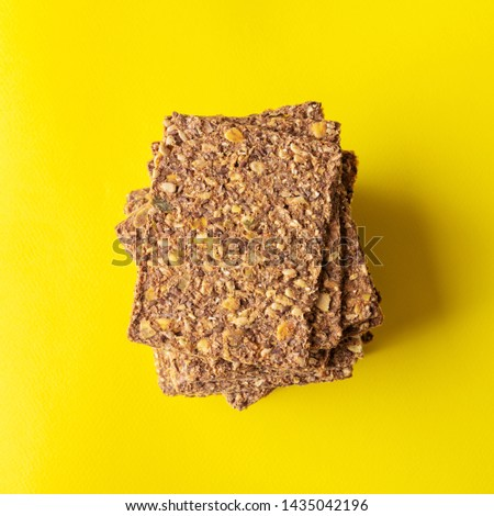 Flat lay of Stack of super-Useful rye multi-grain whole-grain crackers with different seeds on a yellow background with space for text. superfoods healthy organic products.