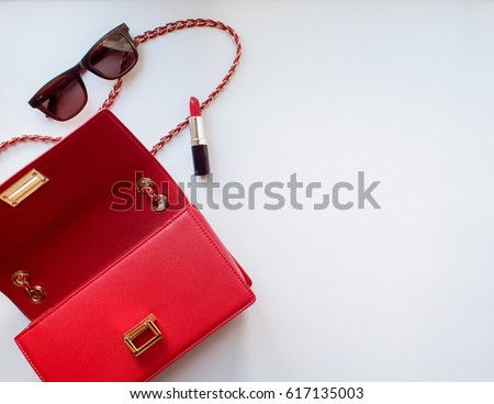 Flat lay of stylish woman accessories, handbag clutch, sunglasses,and a red lipstick on white background with copy space #617135003