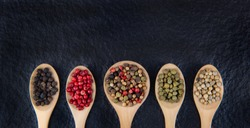 Flat lay of 5 types of peppercorn in a wooden spoon on a black background Healthy food concept