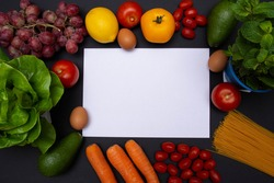 Flat lay of various vegetables and fruits on black background, white blank paper in the center with copy space, caption space, mockup