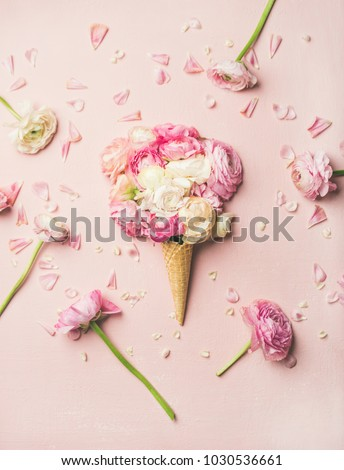 Flat-lay of waffle sweet cone with pink and white buttercup flowers over pastel light pink background, top view. Spring or summer mood concept